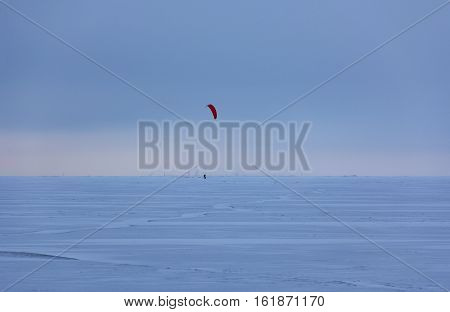 kajtserfingom athletic riding in the winter on ice and snow through the Gulf of Finland on the sunset coast of St. Petersburg kitesurfing kiteboarding