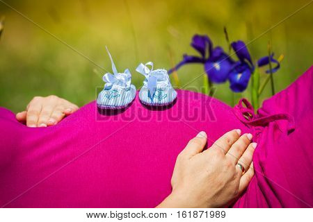 Pregnant woman lying on a grass with baby shoes on her belly