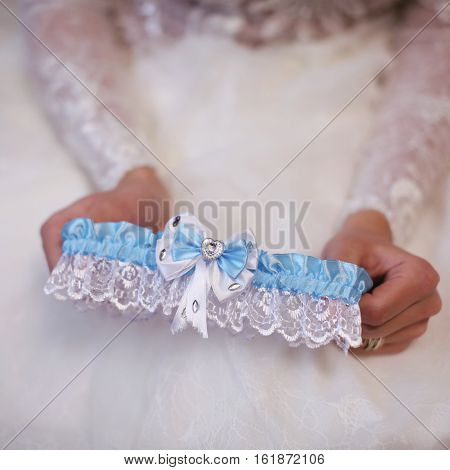 Garter in the bride's hands close up.