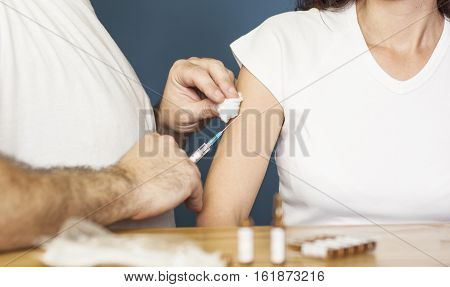 Doctor holding a syringe and preparing to vaccinate a women against flu