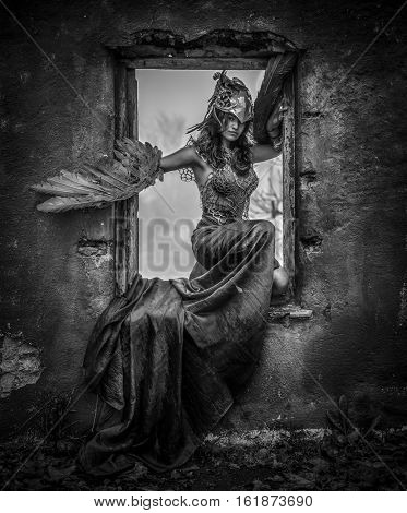 Glamour, Beautiful young woman with dress made of blue feathers, angel fallen from heaven to earth. Picture of fantasy and short stories, Sitting in the frame of an old window