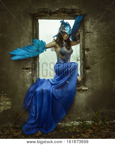 Beautiful young woman with dress made of blue feathers, angel fallen from heaven to earth. Picture of fantasy and short stories, Sitting in the frame of an old window