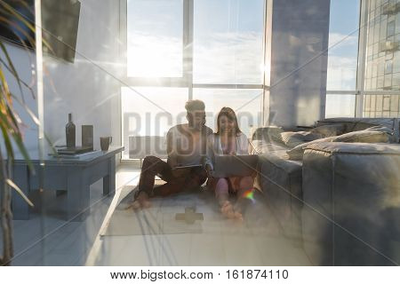 Young Couple Sitting On Floor Using Laptop Tablet Computer Modern Apartment Big Panoramic Window Sea View, Mix Race Man Woman Morning Home Interior