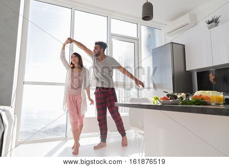 Young Couple Dancing In Kitchen, Lovely Asian Woman And Hispanic Man Modern Apartment With Big Windows Interior