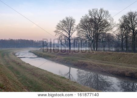 Dutch Misty Rural Landscape With River And Bare Trees. Nature Reserve Needse Achterveld. Gelderland.