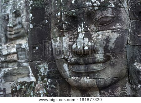 A horizontal photographic image of 2 large sculpted stone faces of the Buddha at Bayon Temple in Angkor Thom which is close to Angkor Wat near Siem Reap in Cambodia.