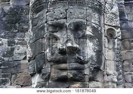 A horizontal photographic image of a large sculpted stone face of the Buddha at Bayon Temple in Angkor Thom which is close to Angkor Wat near Siem Reap in Cambodia.