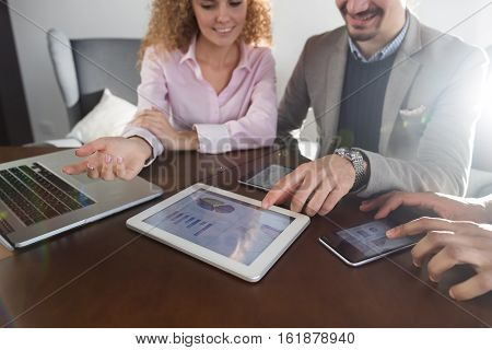 Business People Team Group Discussing Financial Diagram Report On Tablet Screen Businesspeople Meeting Sitting At Desk Coworkers Office Pointing Ginger Graph