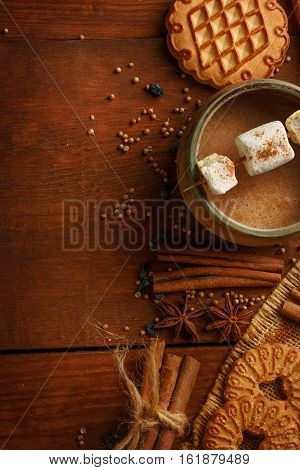 Composition of cocoa in cup with marshmallow biscuit cookies anisetree stars cinnamon barks dried barberries burlap and spices on brown wooden background. Copyspace.