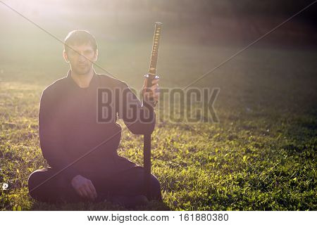 Sitting black ninja with his sword at sunset light on green grass background.