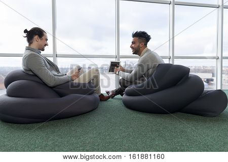 Two Business Man Using Tablet Computer Coworking Center Business Team Coworkers Sitting in front Big Panoramic Window Modern Office