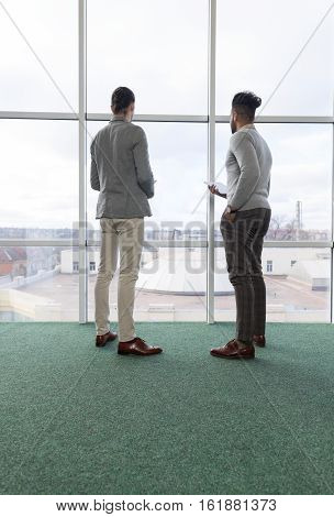 Two Business Man Using Tablet Computer Coworking Center Business Team Coworkers Stand in front Big Panoramic Window Modern Office