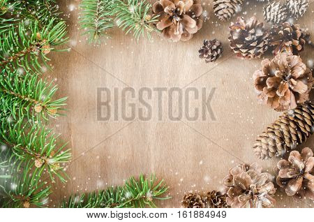 Christmas Background. Cones and Branch fir tree in a frame on rustic wooden table with copy space. Top view. Copy space. Selective focus. Snow effect.