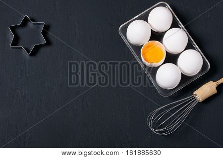 Dark wooden baking background with eggs whisk and star shape cookie cutter. Horizontal orientation with copyspace top view.