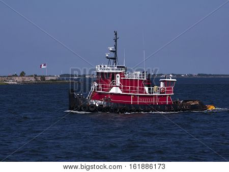 Red tug boat plies the waters of the harbor of Charleston, South Carolina on a crisp Spring day
