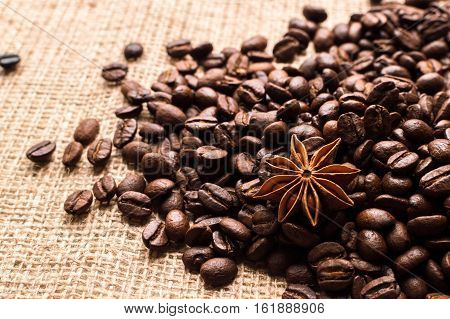 Coffee beans and badian on the sackcloth background.