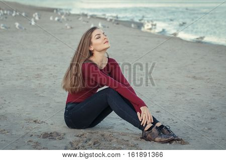 Lifestyle portrait of Caucasian young beautiful woman with closed eyes long hair in black jeans and red shirt sitting on sand on beach among seagulls birds on autumn fall sunset