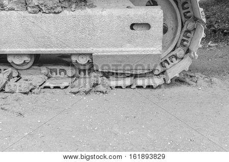 iron Crawler Loader wheels on dirty ground black and white tone