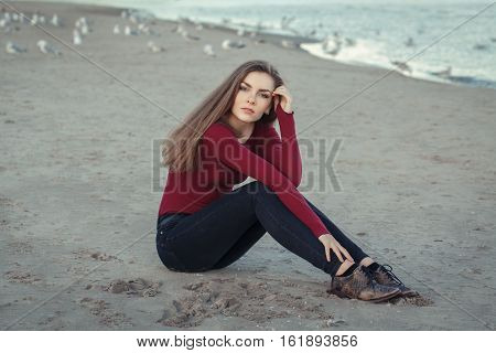 Lifestyle portrait of Caucasian young beautiful woman with long hair in black jeans and red shirt sitting on sand on beach among seagulls birds on autumn fall day outdoor at sunset