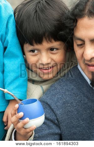 Portrait little boy wiht father in the street drinking mate