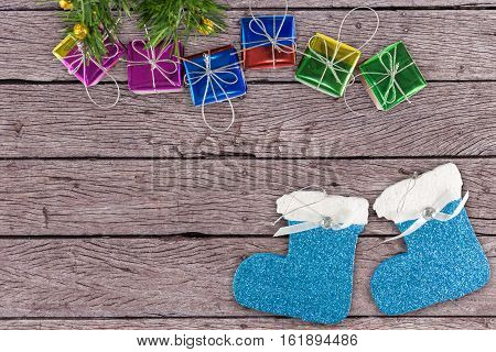 Christmas decoration gift boxes and foam socks on wooden table background with drop shadow
