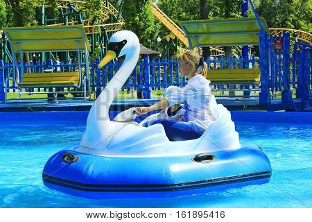 happy children and their parents ride water catamarans inflatable in Gorky park in Kharkiv