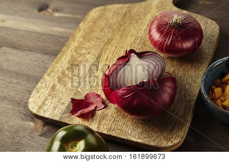 Red bisect onion tomato herbs and spice on wooden table.