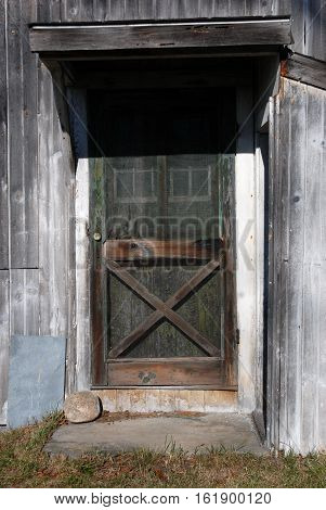 Old screen door on the side of a barn with rusty screen and algae on door.\