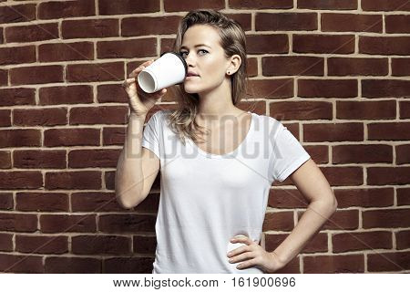 Beautiful blonde woman drinking coffee in paper blank cup takeaway. Wearing white t-shirt. Bricks wall background