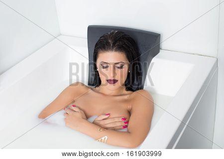 Sexy brunette woman posing in milk bath