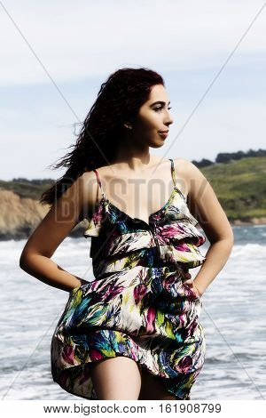 Hispanic Woman Outdoors Standing In Dress At Ocean