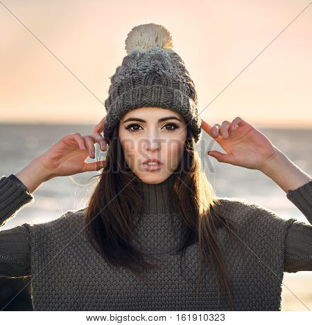 Beautiful young woman wearing grey knitted hat and warm knitted sweater posing outdoors and looking in camera