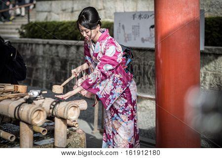 TOKYO, JAPAN - NOVEMBER 10, 2016: Young women wearing traditional japanese kimonos at Fushimi Inari Shrine in Kyoto, Japan. Kimono is a Japanese traditional garment.