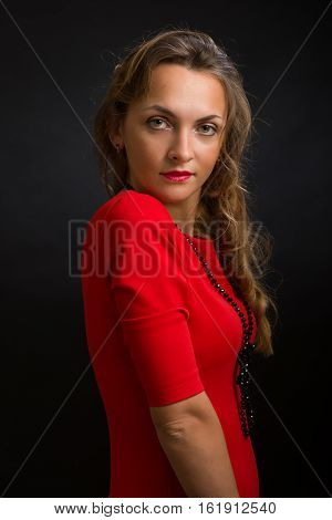 The young beautiful woman in a bright dress of scarlet color with a black beads on a neck and ringlets against a dark background