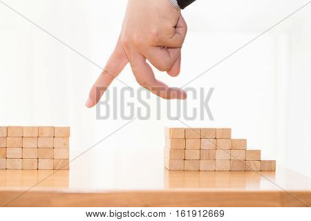 Hand jump through the gap between wood block Jump over obstacles concept
