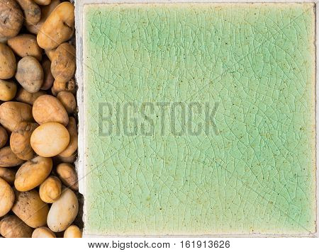 close up background and texture of stretch marks cracked on emerald green glazed tile with brown gravel