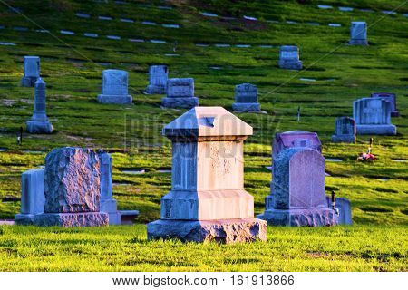 Vintage stone headstones in an old cemetery with a manicured green lawn