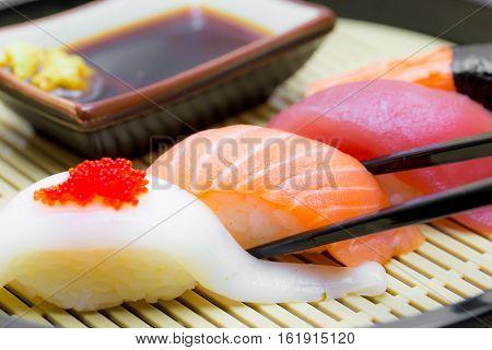 Sushi with chopsticks black wasabi and shoyu sauce