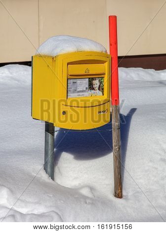 Engelberg, Switzerland - 9 March, 2016: a Swiss Post box covered by snow. Swiss Post is the national postal service of Switzerland, being a public company, headquartered in the Swiss city of Bern.