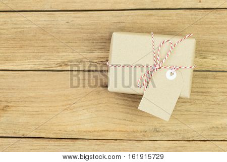 Gift box wrapped in recycled paper on wood background