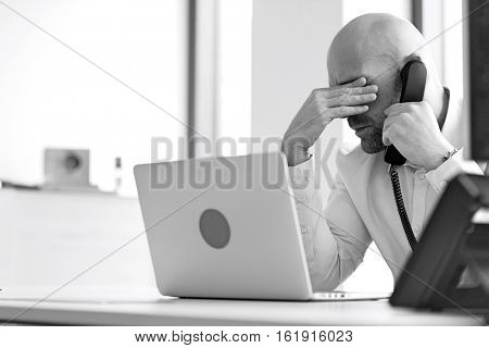 Tired mid adult businessman using telephone at desk in office