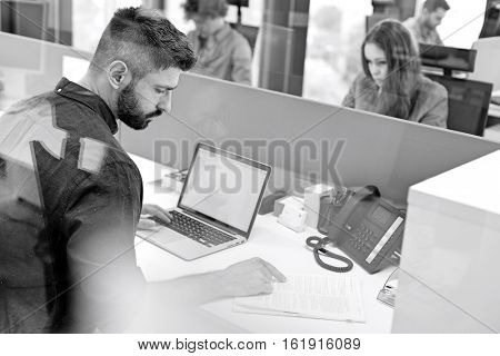 Mid adult businessman reading book while using laptop in office