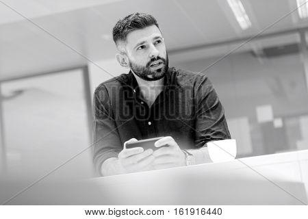 Mid adult businessman holding smartphone while looking away in office