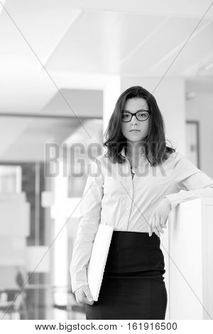Portrait confident young businesswoman holding book in office