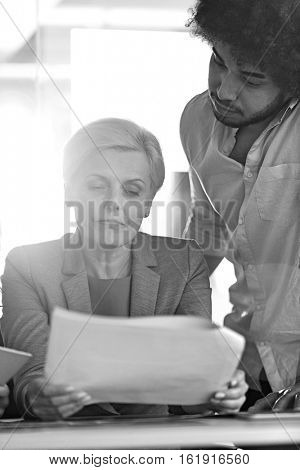 Businessman and businesswoman reading document in office