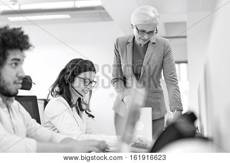 Mature businesswoman assisting female operator in office