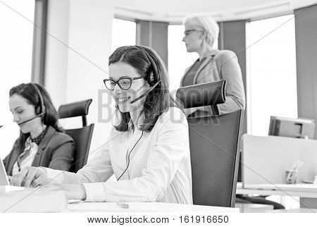 Female customer service representative using headset while colleagues in background at office
