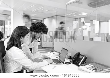 Young businessman and businesswoman using laptop at desk in office