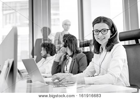 Portrait of smiling customer service representative using laptop while colleagues in background at office