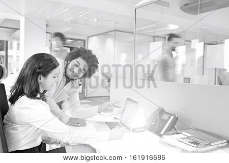 Young businessman and businesswoman discussing over laptop in office